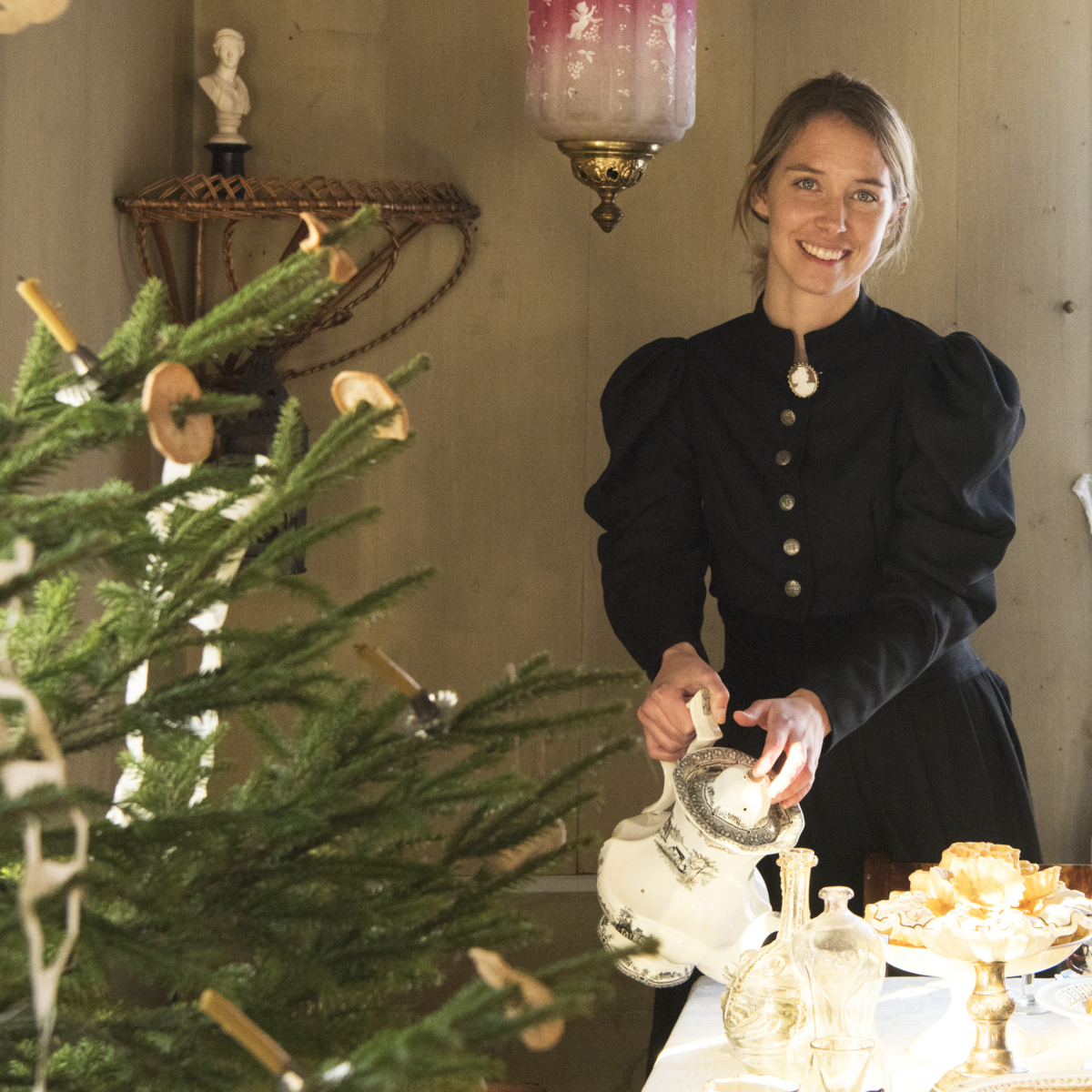 Woman pouring coffee from a silver pot next to a Christmas tree decorated with old christmas candles and dry apples.