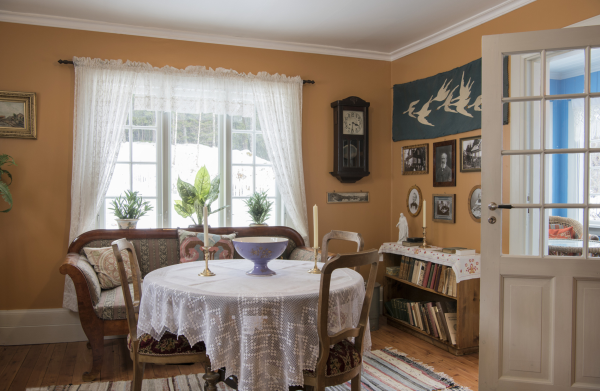 The living room in the 1920s house at Maihaugen with yellow painted walls and varied interior.