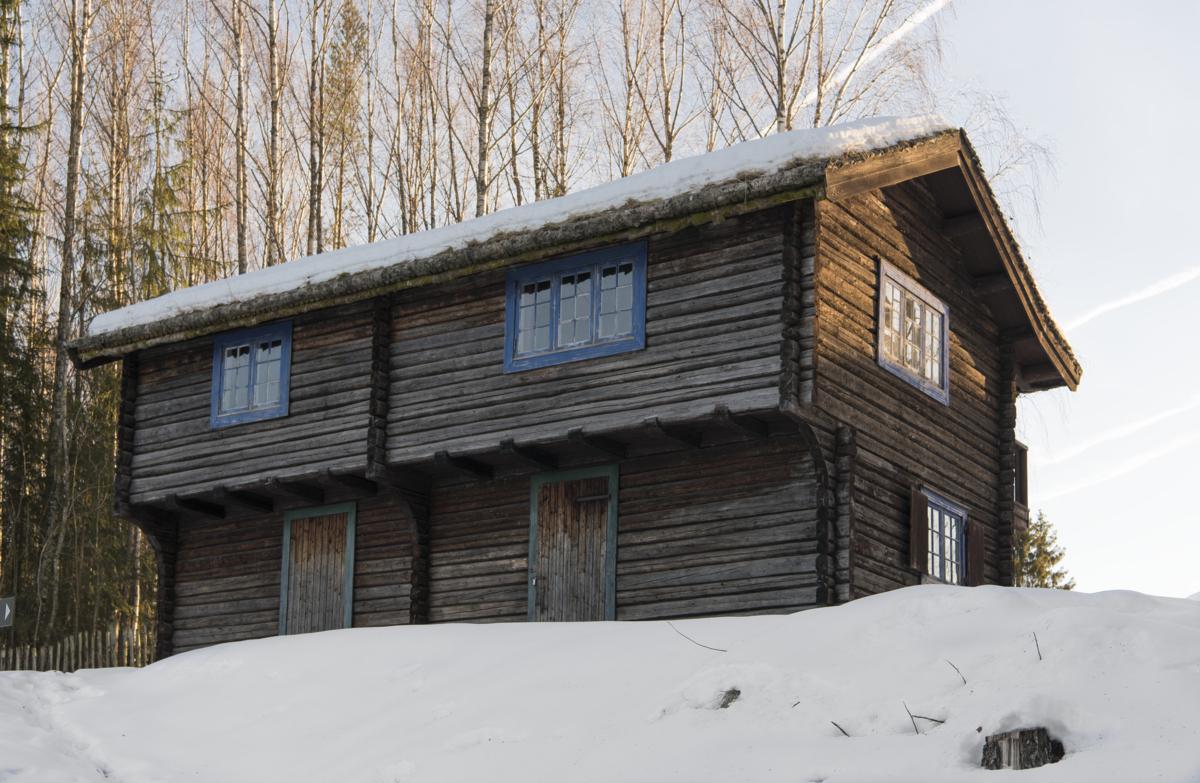 Laftet hytte med blå vinduer.