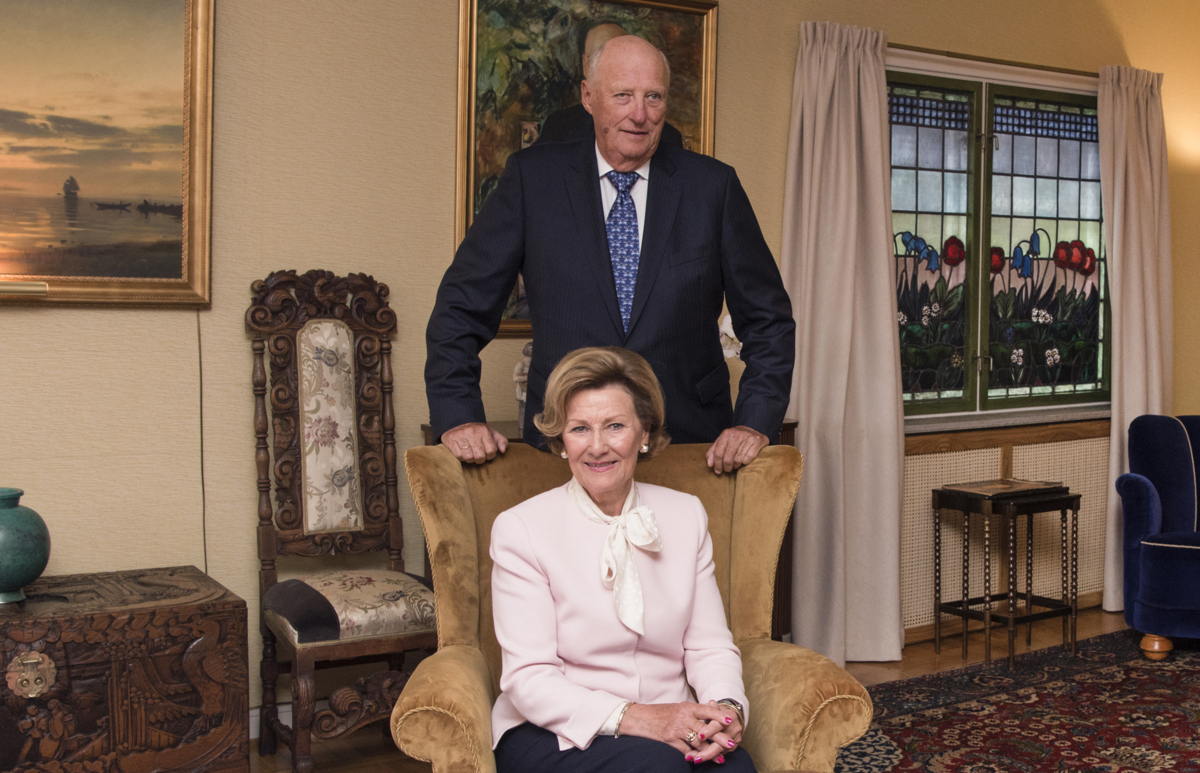 Norway's Queen Sonja sitting in a chair with King Harald standing behind in the living room of the Queen's childhood home at Maihaugen open-air museum in Lillehammer.