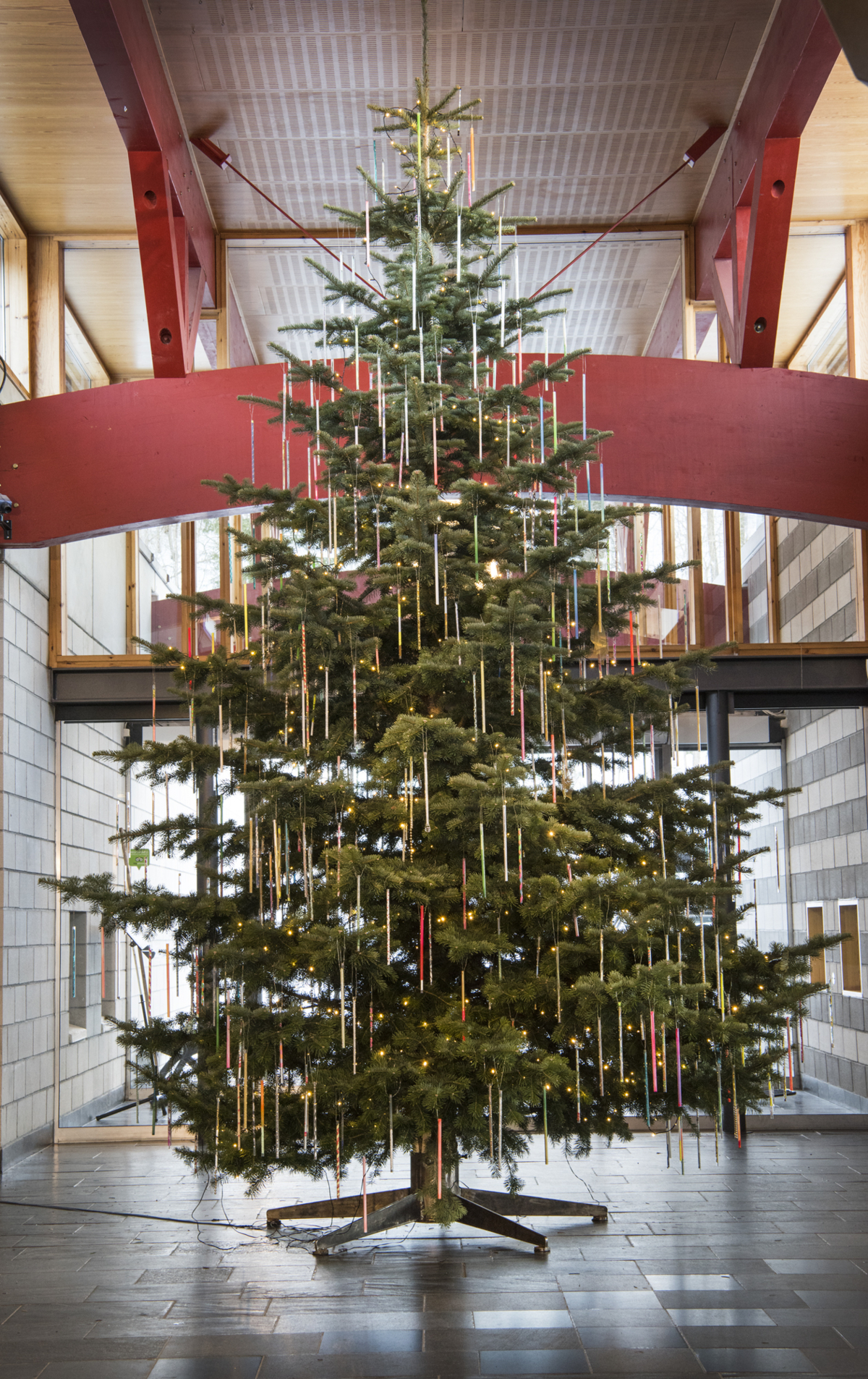 Large Christmas tree decorated with glass cyllinders in different colors.
