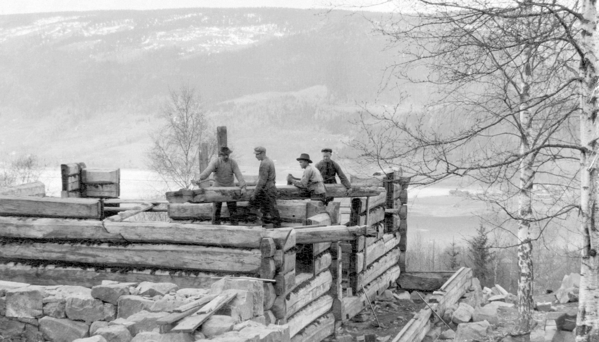 Historisk foto av menn som lafter et hus.