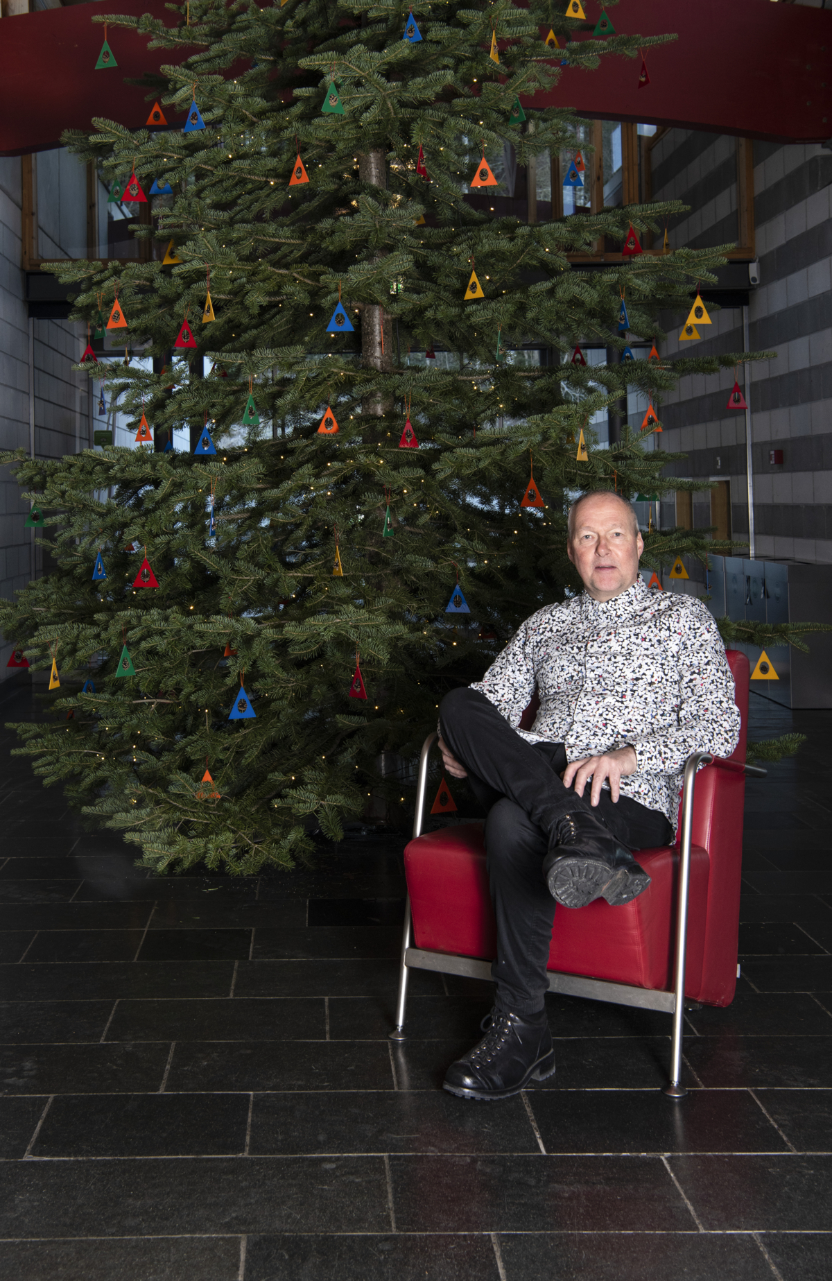 Artist Sigurd Bronger in a red chair in front of the Christmas tree with colorful triangles with pine cones.