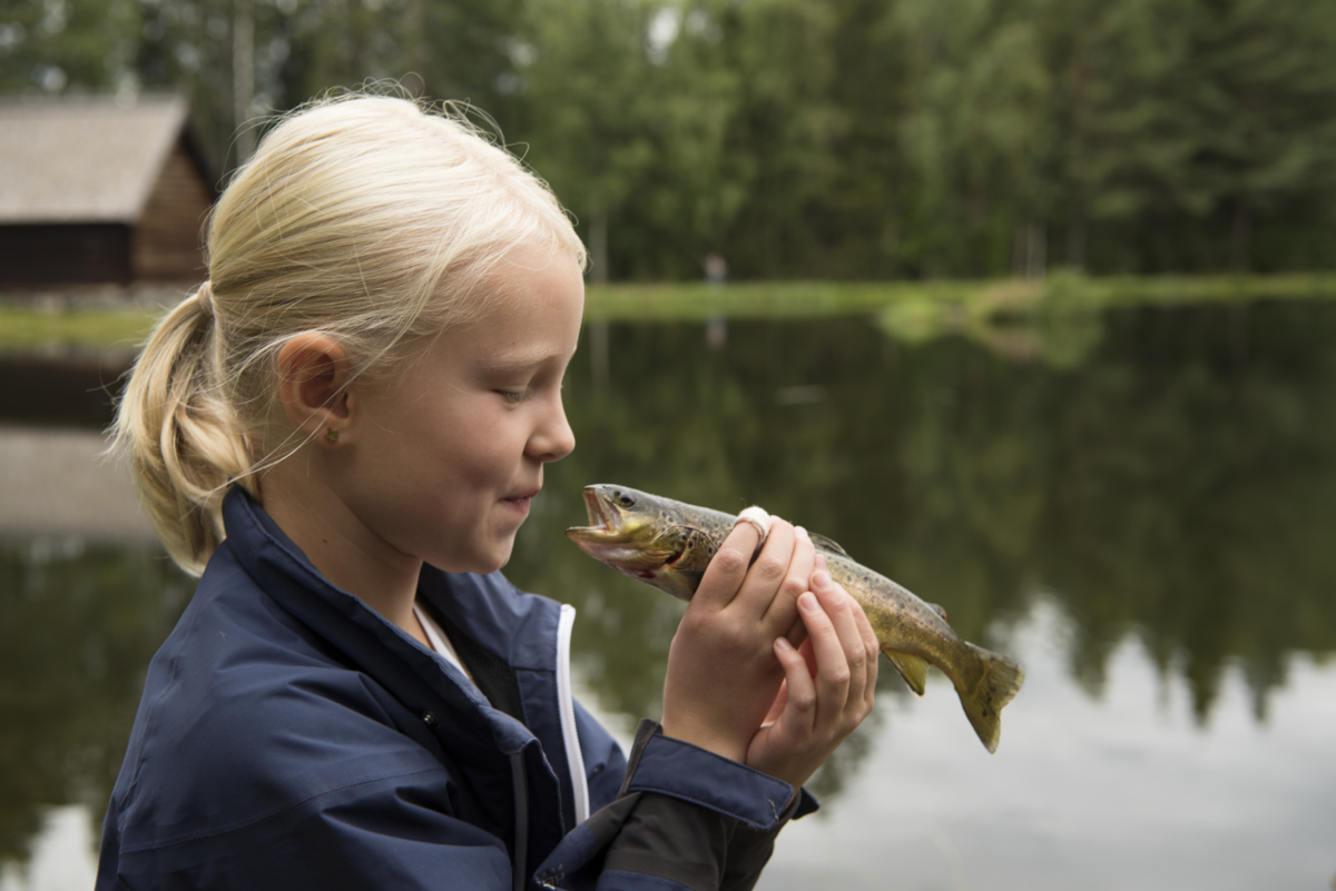 Girl holds a fish towards her face like she is about to kiss it.