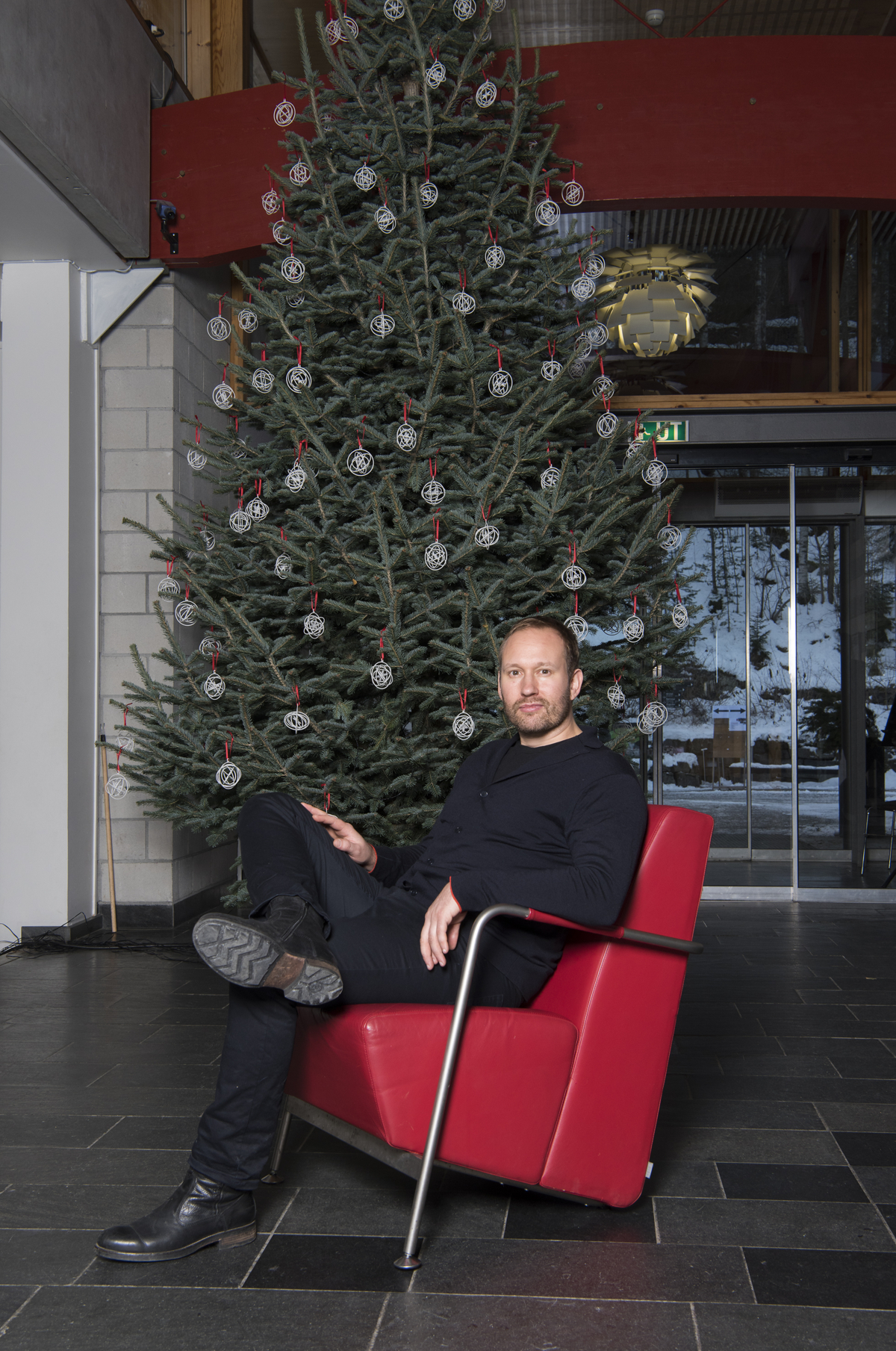 Torbjørn Anderssen sitting in front of a Christmas tree decorated with white ornaments.
