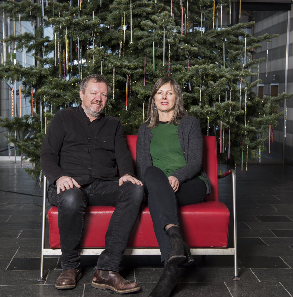Kjetil Trædahl Thorsen and Jorunn Sannes from Snøhetta sitting in a red chair in front of the Christmas tree.