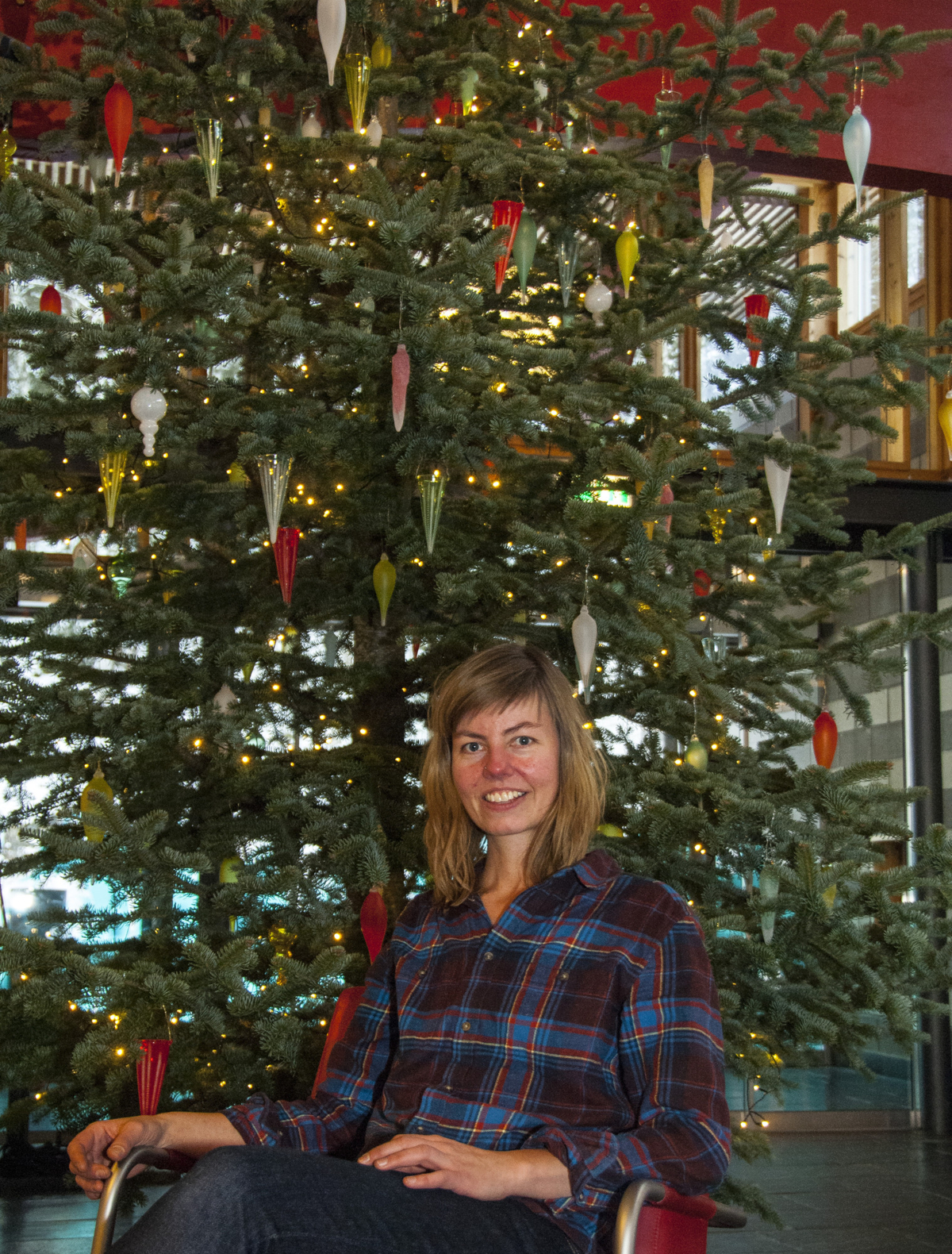 Kari Mølstad in front of a Christmas tree with glass ornaments in different colors.