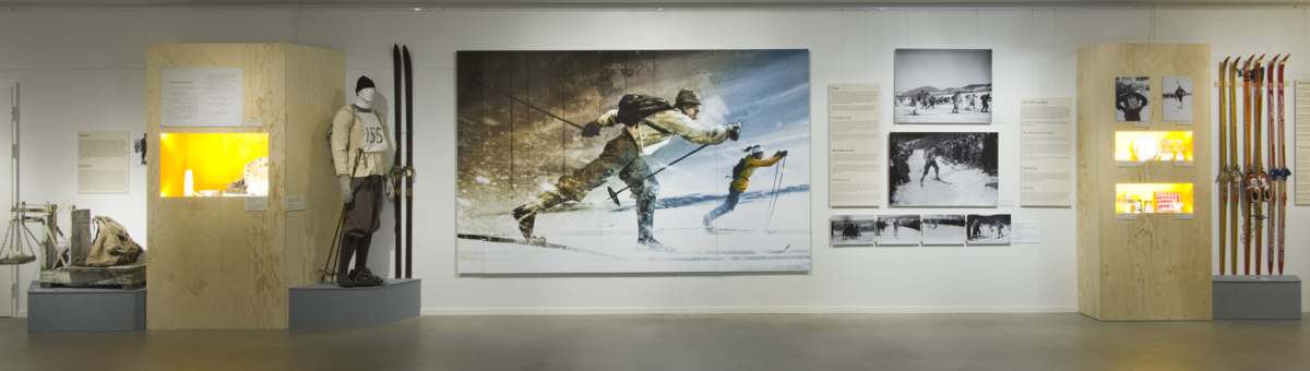 Exhibition room with large illustration on the wall of a female cross-country skier with modern equipment racing from a a male skier with older equipment. There are also several photos, display cases and old skis displayed.