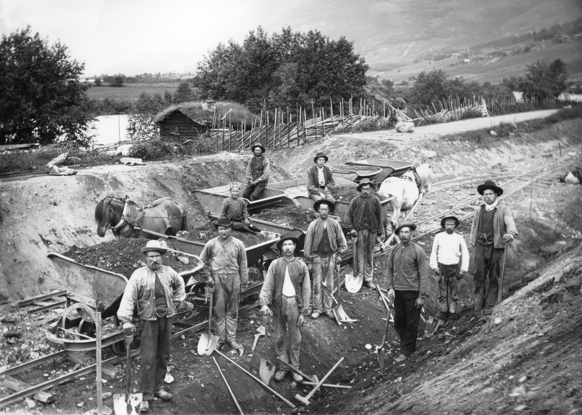 Men with med spades working with the railway. Horses pulling wagons with dirt at the railway tracks.