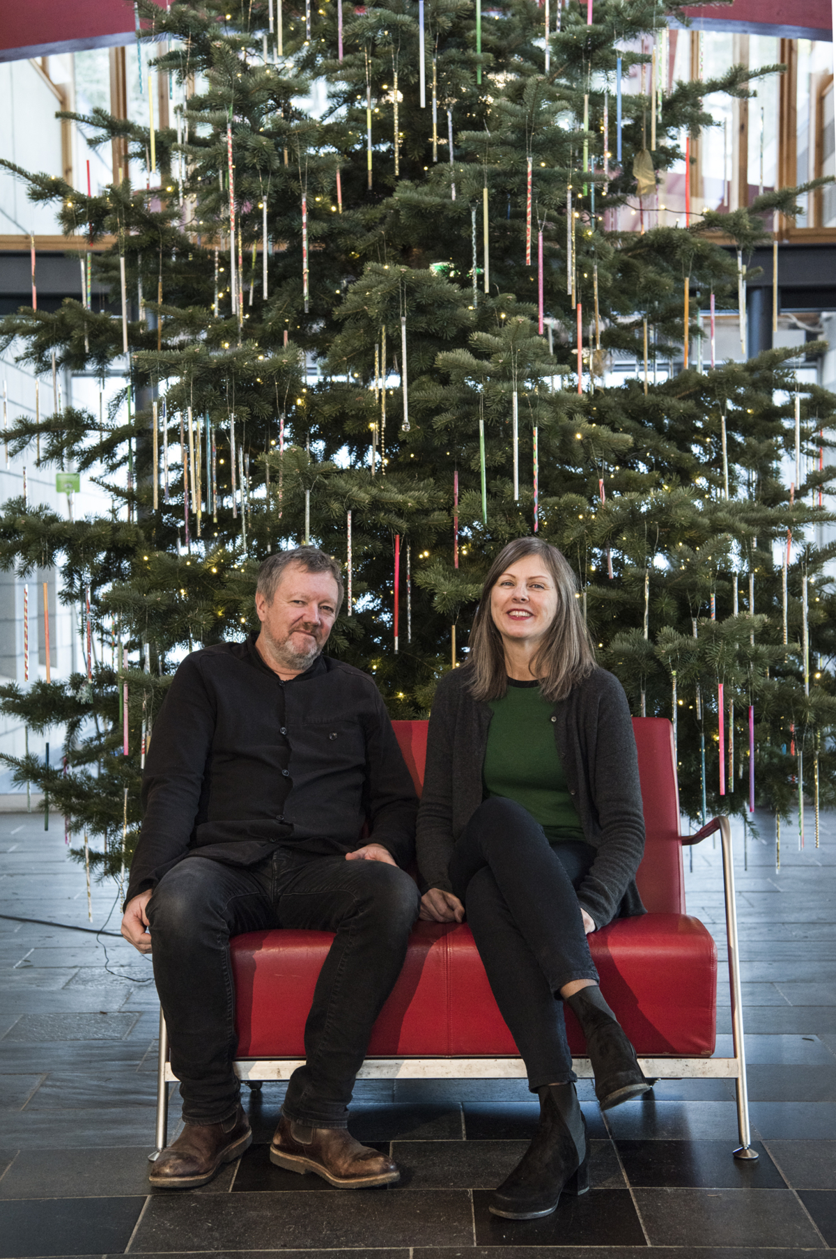 Kjetil Trædahl Thorsen and Jorunn Sannes from Snøhetta i a red chair in front of a decorated Christmas tree.