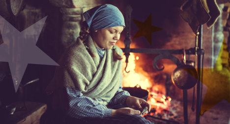 Young woman in historical costume by the fireplace at Maihaugen.
