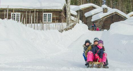 Barn aker på kjelke ved tømmerhus på Maihaugen.