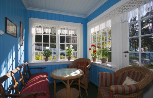 Blue walls and potted plants in the windows of the glassed-in veranda at the 1920s house in the open-air museum Maihaugen in Lillehammer.