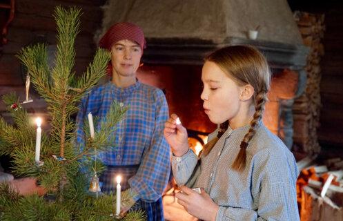 Jente i historiske klær blåser ut en fyrstikk etter å ha tent stearinlys på juletreet.