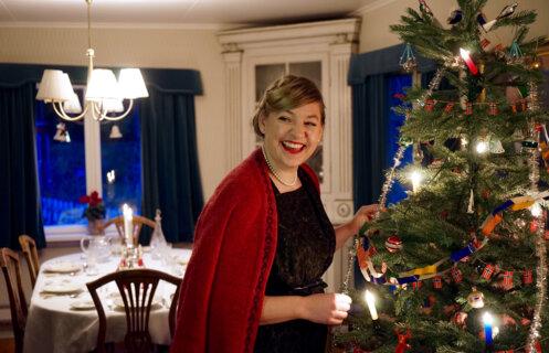 Kvinne i 1950-talls juleantrekk pynter juletreet.