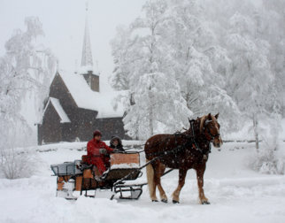 Horse sleighing in front of Garmo stave church at Maihaugen a snowy winter day.