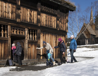 Family on their way into a timber building at Maihaugen.
