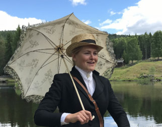 Fine lady with a hat and a lace umbrella in front of the mountain farms at the open-air museum Maihaugen in Lillehammer.