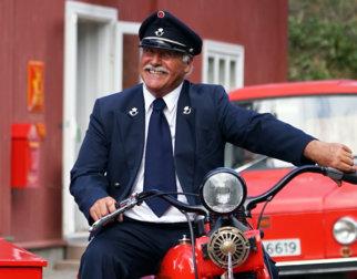 Postman at a historical red postal motorcykle with side car at the Norwegian Postal Museum at Maihaugen.
