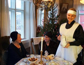 Tjenestepike med kaffekanne i juleselskap.