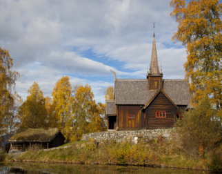 Old stave church surrounded by trees in autumn colors.