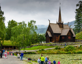 Garmo stave church with visitors and a lake in front, at Maihaugen open air museum.