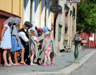 Children dressed in clothes from the old days gathering around a young man in a costume from the old days, in the main street in the Town at Maihaugen open air museum.