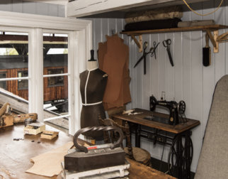 The tailor's workshop with historical equipment like sewing machine, iron, scissors and more.