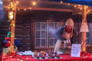Jente selger glaserte epler på Maihaugen, Lillehammer.