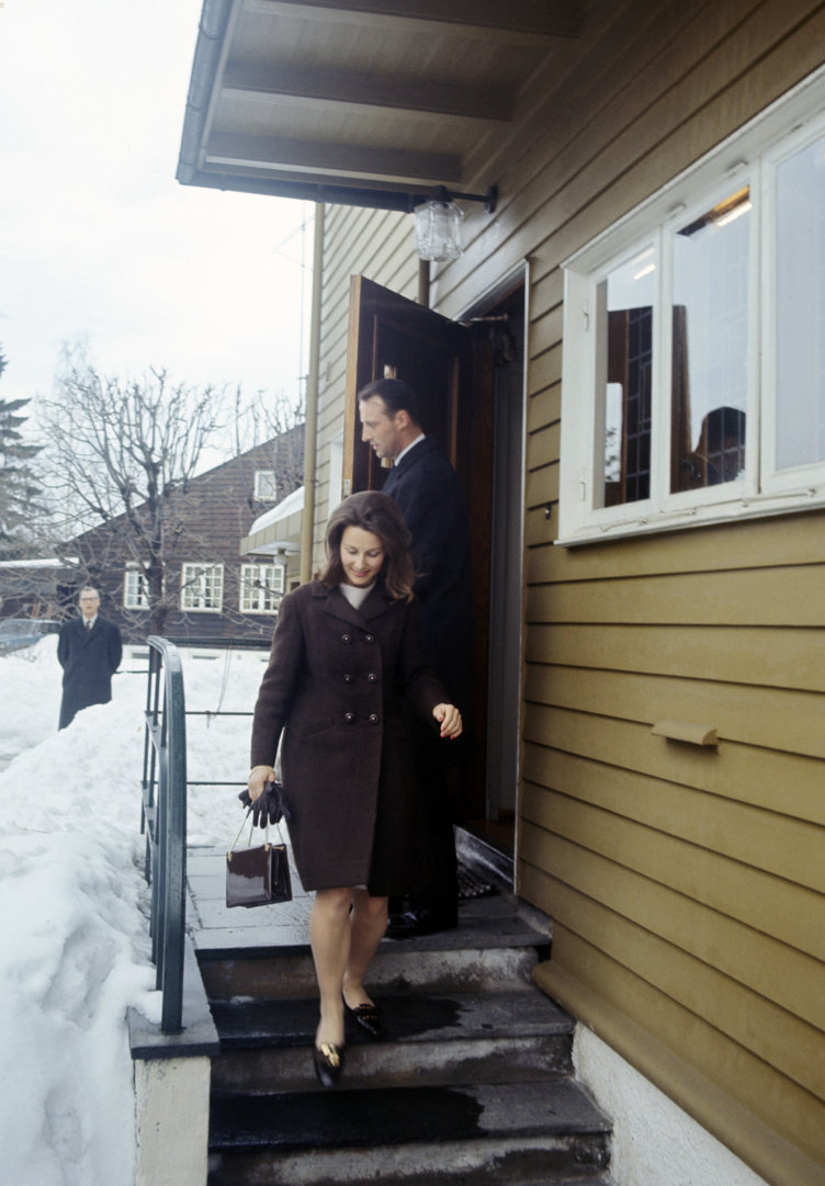 Crown Prince Harald and Sonja Haraldsen on the doorsteps of a house.