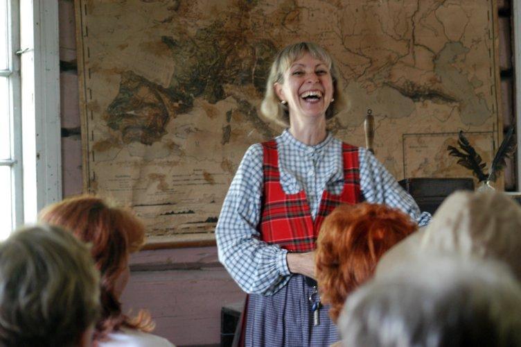 Glad lærerinne i skolestua på Maihaugen, Lillehammer