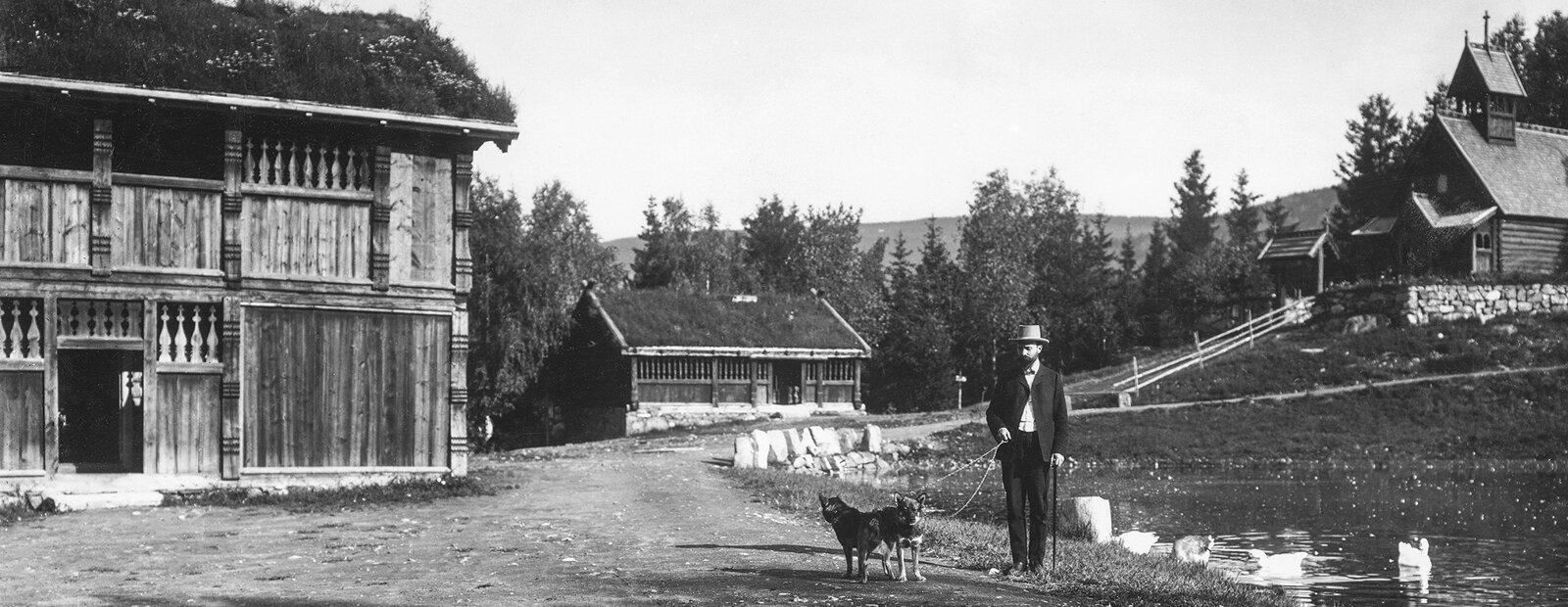 Sort-hvitt foto av Anders Sandvig med flosshatt og hund i bånd.
