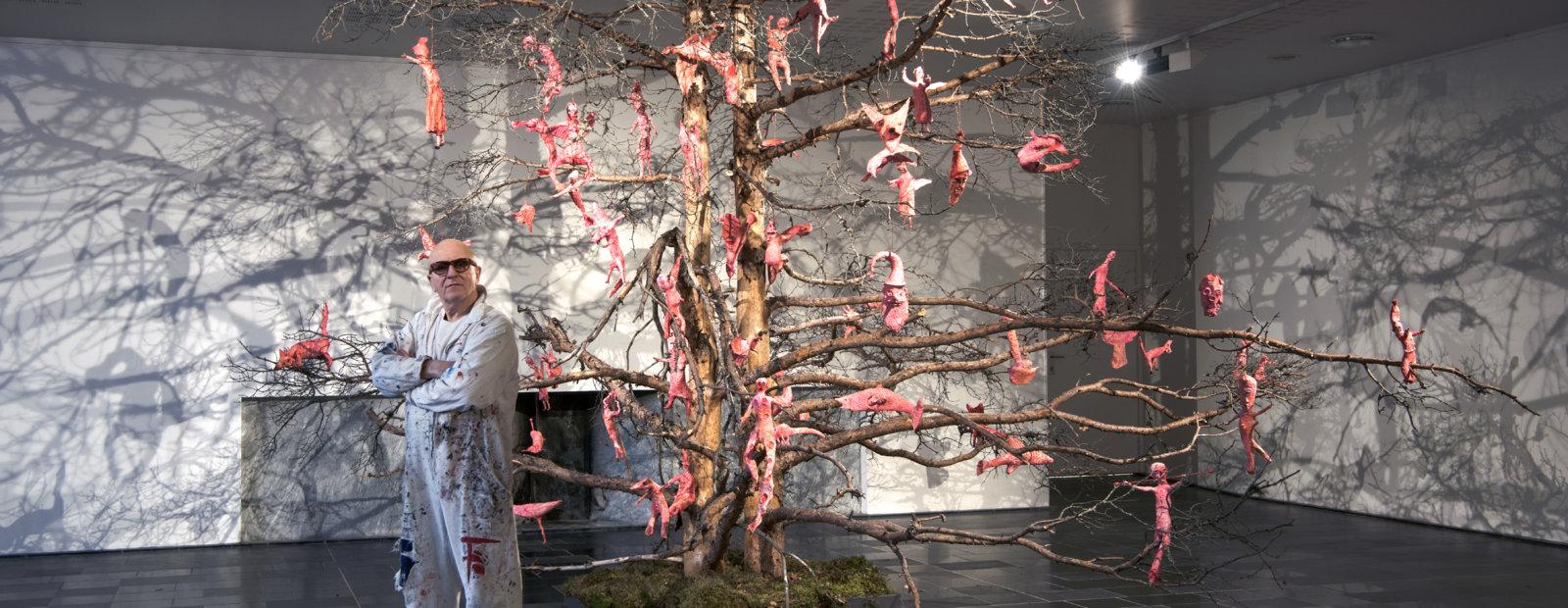Kjell Erik Killi-Olsen in front of a dead pine with pink figures.