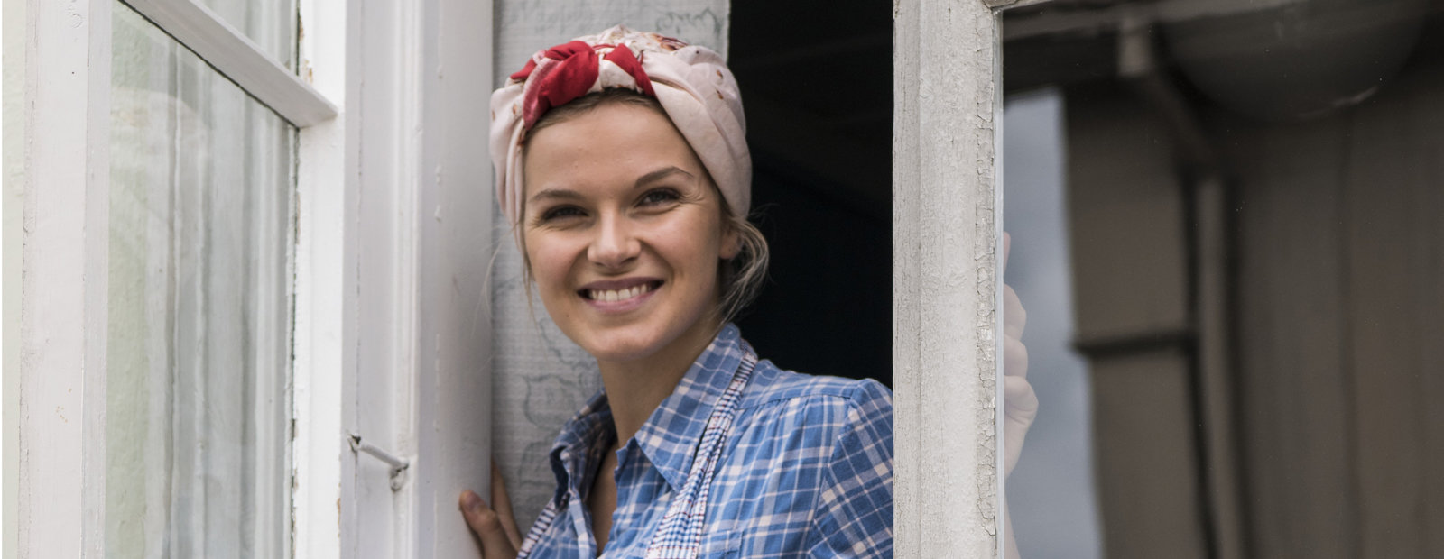 Young woman with a head scarf and apron smiling out of an open window.