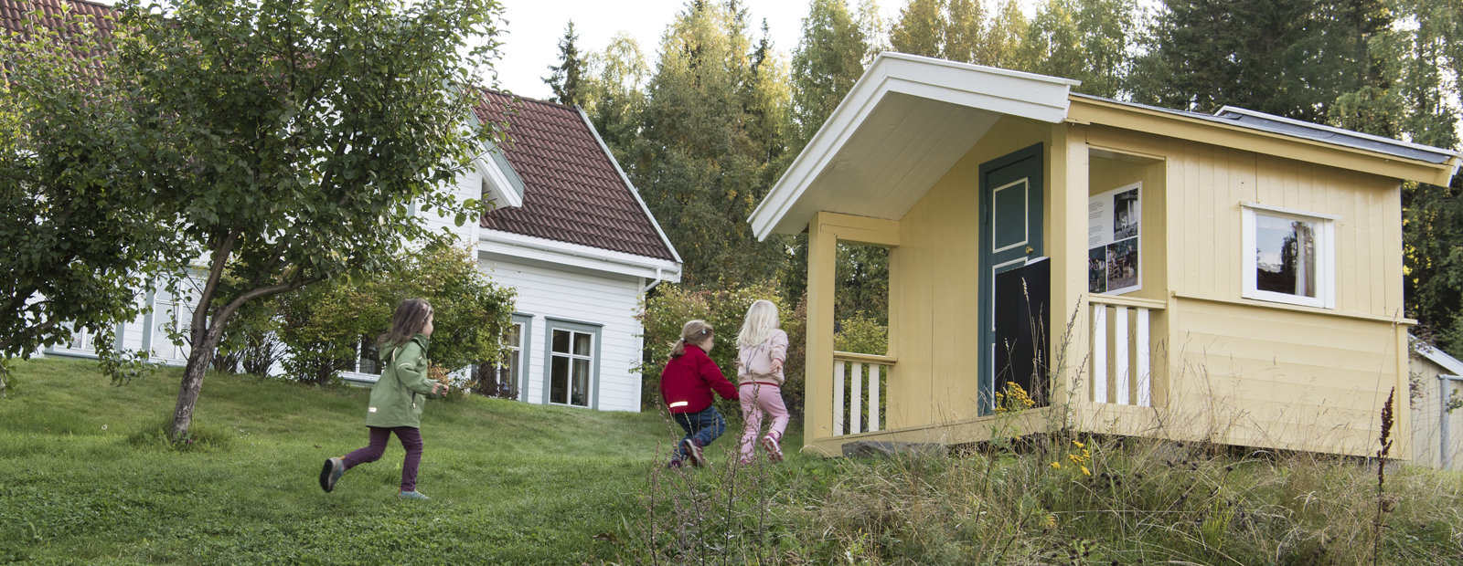 Children running to a yellow play house from the 1950s in the Residential area in the open-air museum in Lillehammer in Norway.