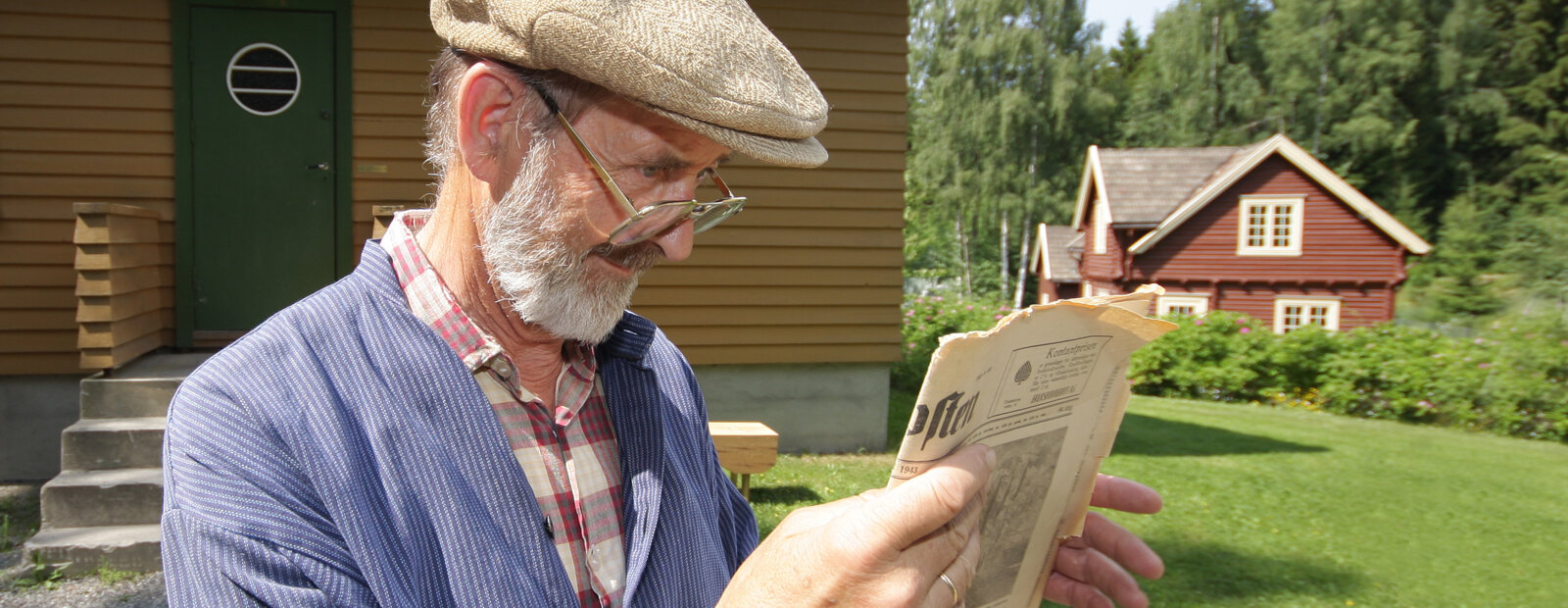 Mann i busserull leser avis utenfor 1940-tallshuset.