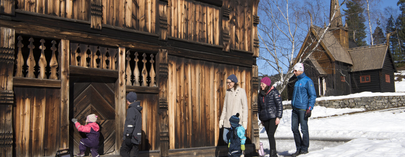 Voksne og barn på vei inn i en gammel laftet tømmerbygning, med Garmo stavkirke i bakgrunnen. På friluftsmuseet Maihaugen i Lillehammer.