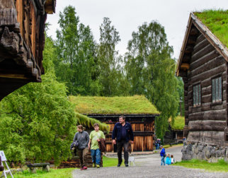 People walking and looking at old timber houses in the open-air museum Maihaugen in Lillehammer.