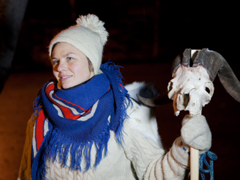Woman dressed up with knitted clothes and a knitted hat, holding a pole with a goat skull.