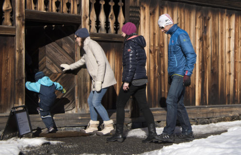 A child and three adults are entering an open historical timber house at the open air museum Maihaugen in Lillehammer in Norway.