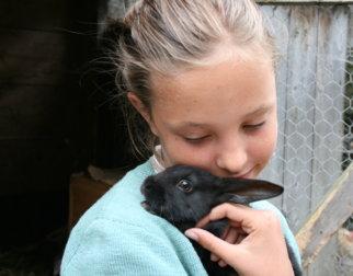 Jente koser med kanin. Foto: Rannveig Urdahl/Maihaugen.